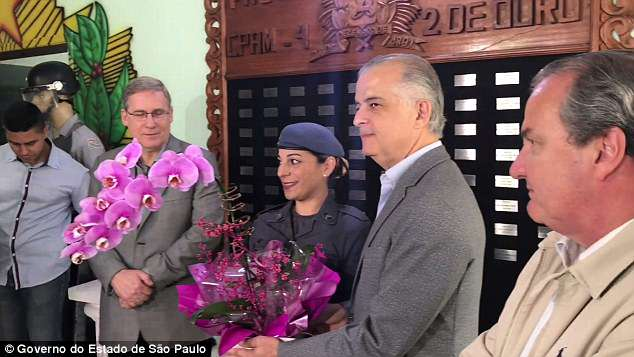 Officer Sastre, who has two daughters, was  presented with flowers by Sao Paulo Governor Márcio França, pictured second right, on Sunday - Mother's Day in Brazil