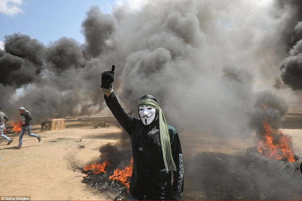 A masked protester holds his hand in the air as he stands in front of burning tyres near the Gaza-Israel border in Khan Yunis
