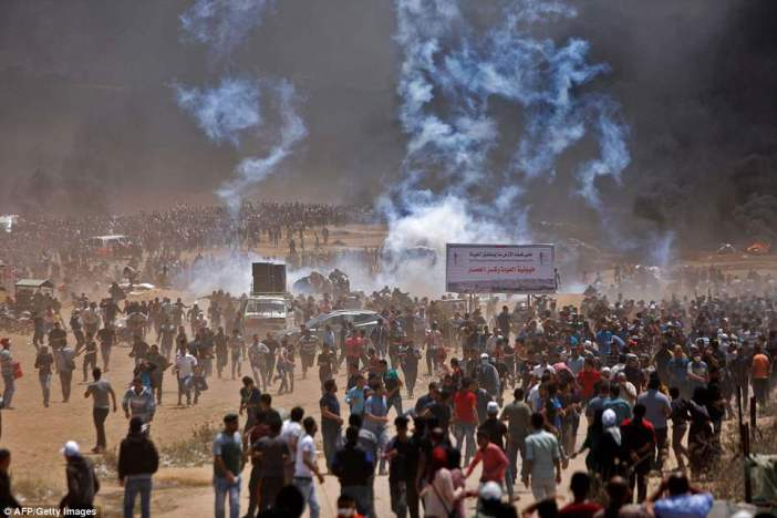 Flashpoint: Tens of thousands of Palestinians gathered for protests against the US embassy opening today and dozens were killed amid clashes with Israeli troops. Crowds are seen sprinting away from tear gas during a clash with Israeli security forces east of Jabalia near the Gaza border