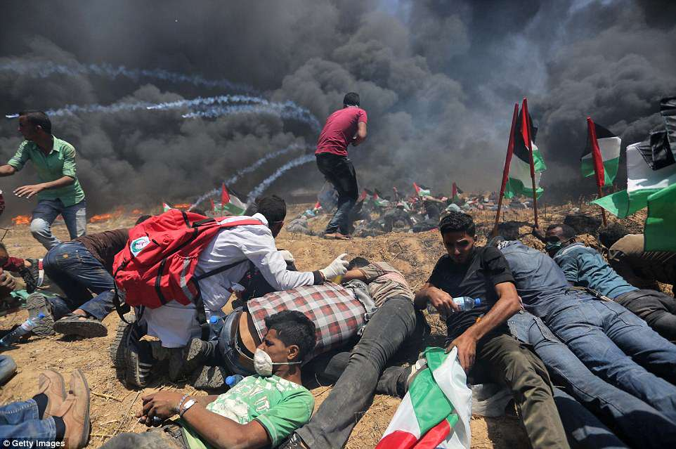 Taking cover: Palestinians throw themselves to the ground as tear gas is hurled towards them during fierce clashes today