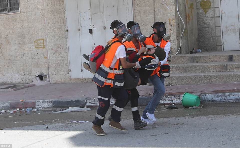 A wounded Palestinian woman is evacuated by men wearing gas masks and high-viz jackets as protests turned violent today