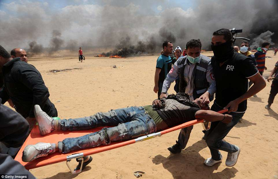 A medic tries to hold an injured man's mouth open as they take him away from the clashes in a stretcher