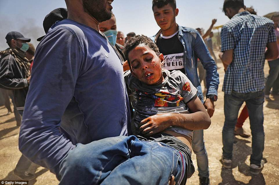 A child who has been affected by tear gas is rushed to medics at the border fence with Israel as mass demonstrations continue along the Gaza border today