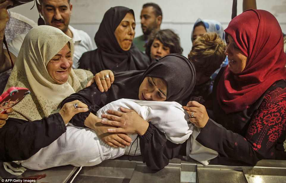 Palestinians are preparing to bury their dead today after 60 people were killed by Israeli forces 'including a baby who breathed in tear gas'. There are claims that a Palestinian baby named as Leila al-Ghandour died as a result of inhaling tear gas during clashes. Harrowing pictures have emerged of distraught family members cradling the baby's body