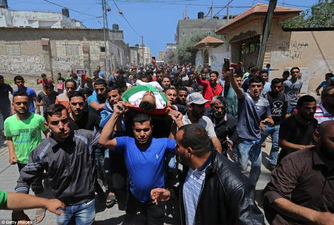 Palestinian mourners carry the body of Muhammed Dividar, killed during clashes in Gaza on Monday, during his funeral at Nuseirat refugee camp in Gaza City
