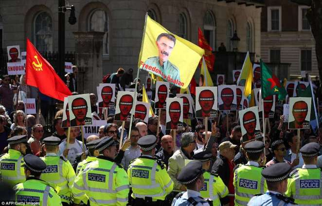 Demonstrators hold placards as they protest against Turkey's President Recep Tayyip Erdogan outside the entrance to Downing Street amid a heavy police presence