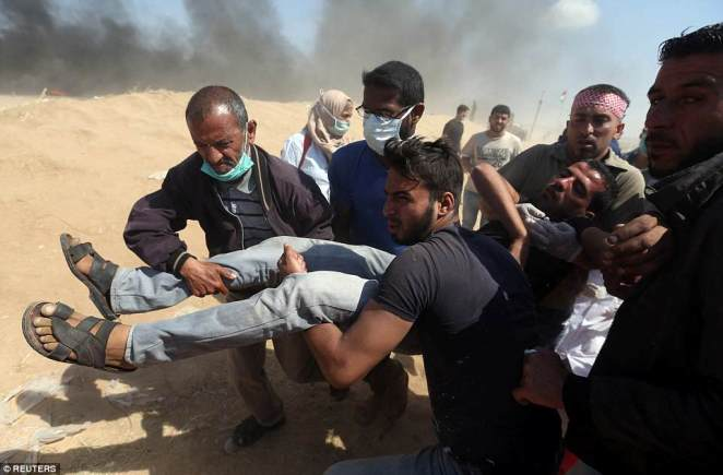 A wounded Palestinian demonstrator is evacuated during a protest marking the 70th anniversary of Nakba, at the Israel-Gaza border in the southern Gaza Strip today