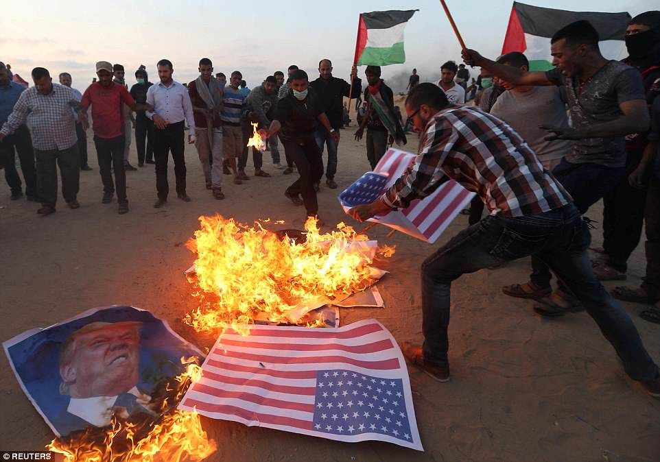 Demonstrators burn pictures of Donald Trump in southern Gaza, at the border with Israel