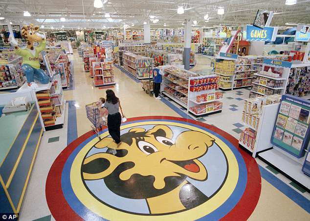 In this July 30, 1996, file photo, a woman pushes a shopping cart over a graphic of Toys R Us mascot Geoffrey the giraffe at the Toys R Us store in Raritan, N.J. Toys R Us