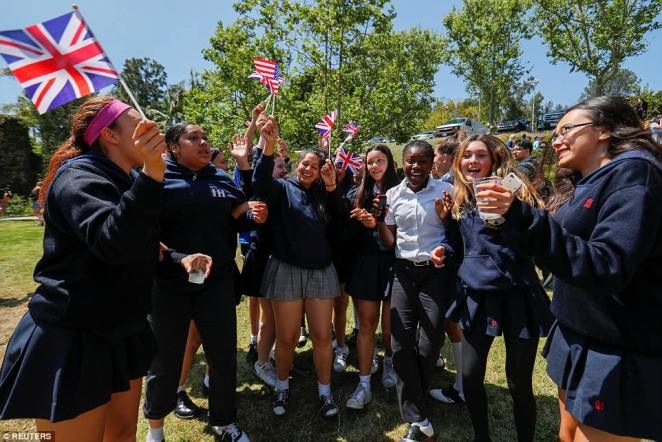 A group of girls joyfully cheer and wave their American and British flags at the 'Here's to Meghan!' celebration on Tuesday
