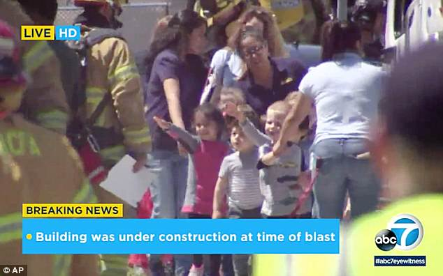 In this photo taken from video provided by KABC-TV, children are evacuated from a preschool across the street from a building that was rocked by the explosion