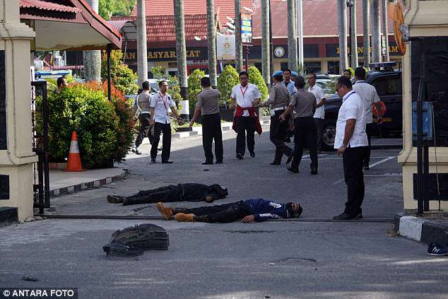 The bodies of two attackers who were shot and killed are seen at the entrance of a police station in Pekanbaru, Indonesia on Wednesday (pictured)