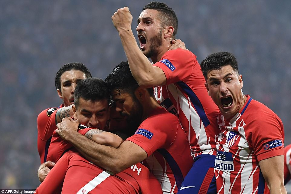 Griezmann is surrounded by his ecstatic Atletico Madrid team-mates as they take the lead over Marseille in Wednesday's final