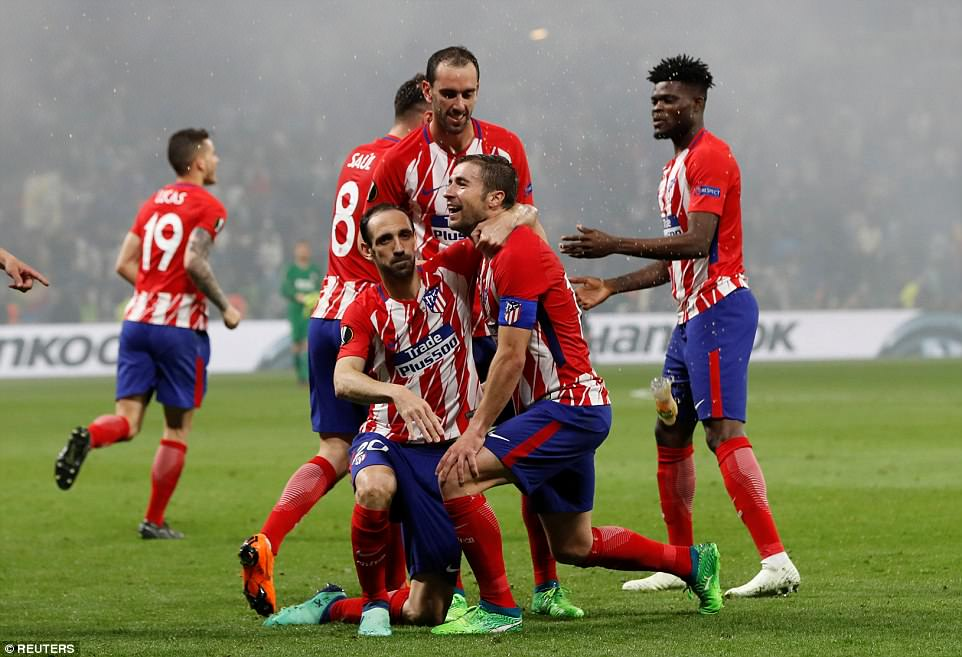 Atletico Madrid players celebrate together as their victory is sealed by a strike from their captain Gabi in the 89th minute
