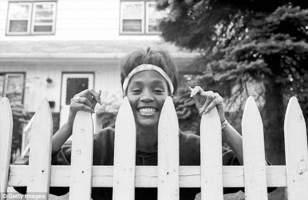 American singer and actress Whitney Houston (1963 - 2012) looks over the picket fence of her mother's home, West Orange, New Jersey in 1985