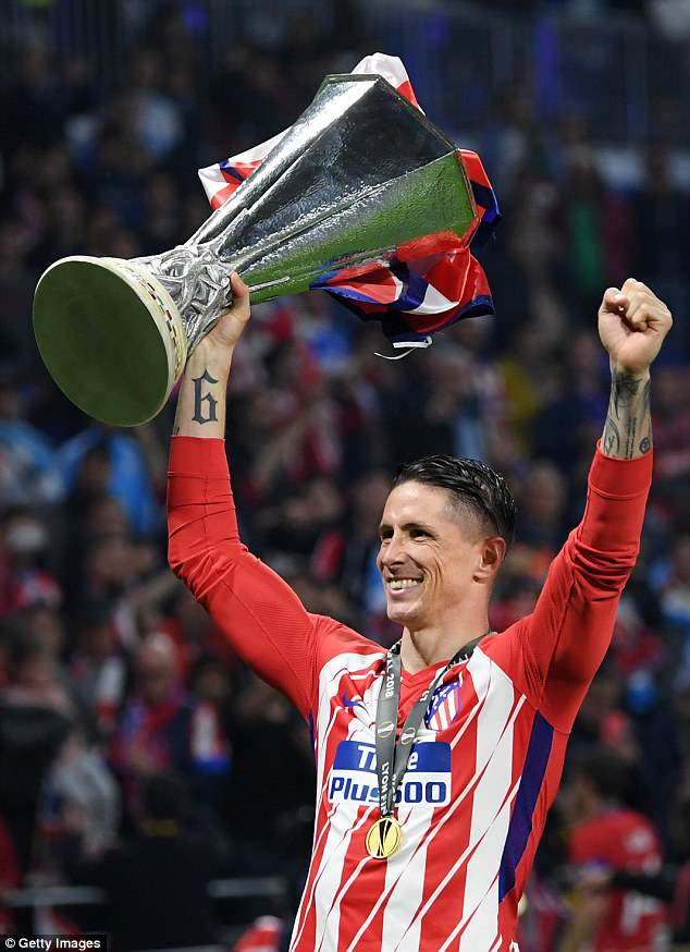 Torres shows off the Europa League trophy having finally won silverware at Atletico