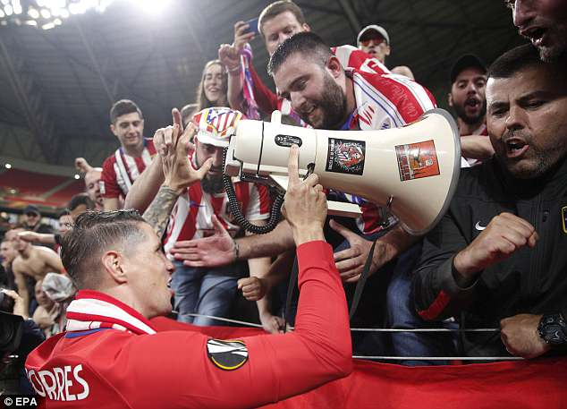 The striker celebrates with Atletico fans after what is likely to be his final appearance for them