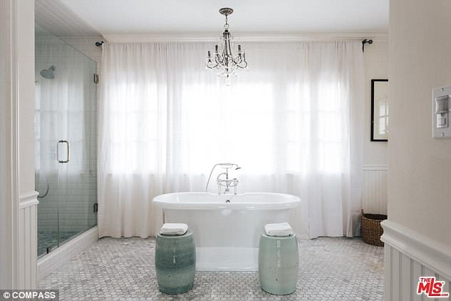 The master bath includes a soaking tub and crystal chandelier