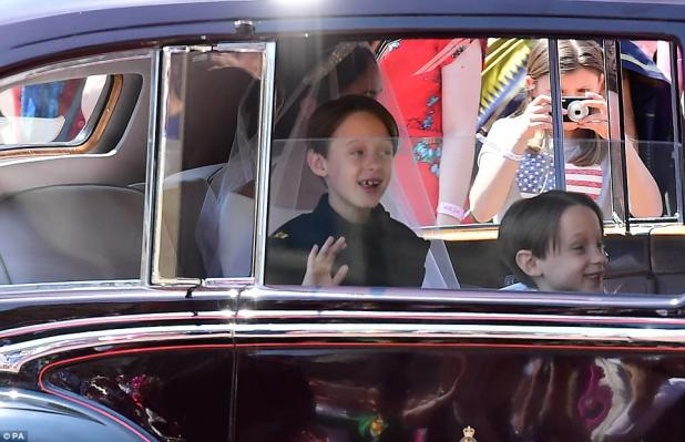 The four page boys, including Prince George, also trailed the bride as two held her metres-long wedding veil as she walked towards Prince Harry