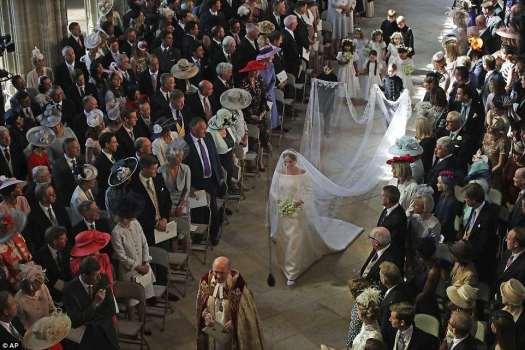 La novia, aturdida con un clásico vestido de novia de seda blanca de Givenchy, bajó por el pasillo de la capilla de San Jorge para casarse con el príncipe Harry.