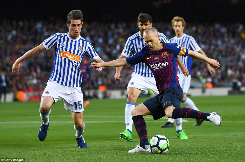 Iniesta of Barcelona competes for the ball with Aritz Elustondo of Real Sociedad during the first half at the Nou Camp
