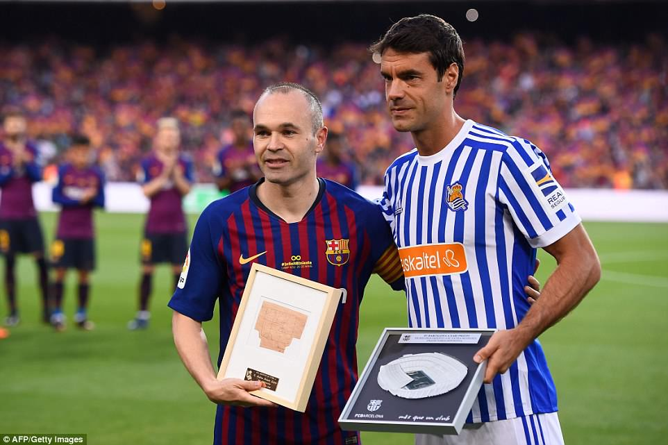Iniesta (left) poses with Xabi Prieto (right) after being presented with pictures to mark his final Barcelona game