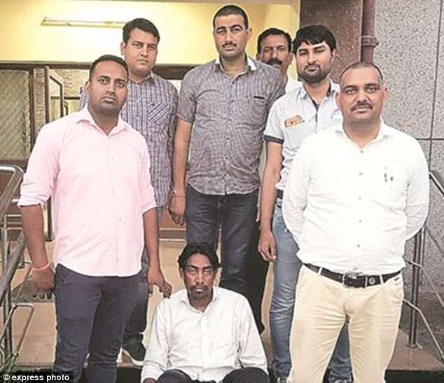 Killer:Manjeet Singh Karketa, 30, pictured sitting centre surrounded by police, ran an agency which found employment for young women as domestic helps and pocketed their salaries