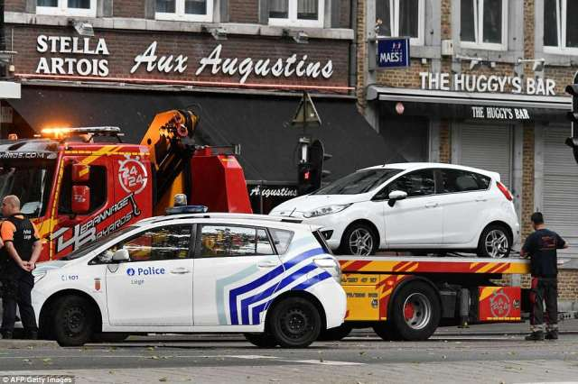 A white car is taken by a tow truck at the scene of a shooting at the boulevard d'Avroy in Liege ater a gunman shot dead three people, two of them policemen