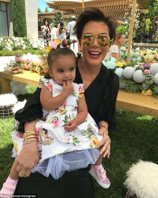 Proud grandma: On Sunday, Kris Jenner cuddled her granddaughter Dream Renee Kardashian, age one, during North West and Penelope Disick's joint birthday bash in Calabasas