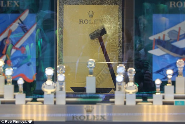 A sledgehammer is shown lodged in the glass of a Rolex display cabinet at Watches of Switzerland on Regent Street