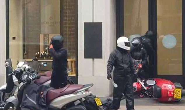 Britain is in the grip of a violent crime wave as thugs run riot on mopeds and motorbikes. Pictured: Scene of thugs breaking into a jewellers in central London on Tuesday