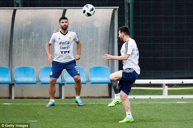 Aguero (L) and Messi (R) smile as they keep the ball up during a training session in Barcelona