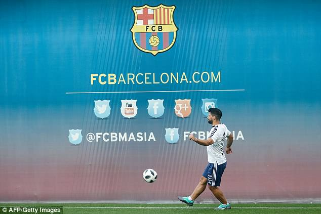 Manchester City's Sergio Aguero passes the ball in front of a Barcelona-themed backdrop