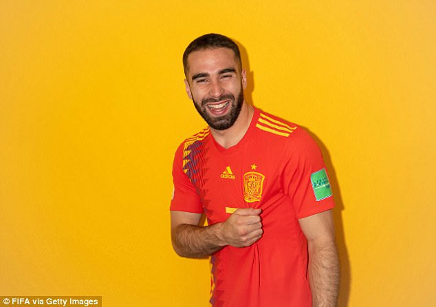 Carvajal continues to smile awkwardly as he grabs his shirt just below the Spain emblem