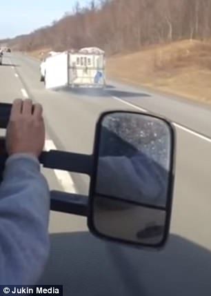Hilarious video has captured a white van driving down a highway with a U-Haul trailer hitched to the back of it but dragging on its side (pictured)