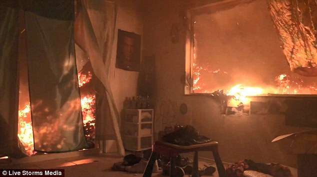 The footage, taken on a camera set up inside the home, shows the ever-creeping wall of lava converging on the property and piling up outside the sliding door and windows