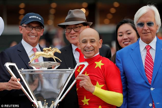 Baffert (far right) is seen after the race with jockey Mike Smith and the owners