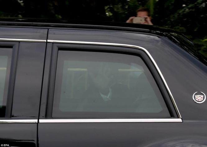 President Trump is seen waving from the window of his limo, which travels with the U.S. president everywhere he goes, in Singapore on Monday