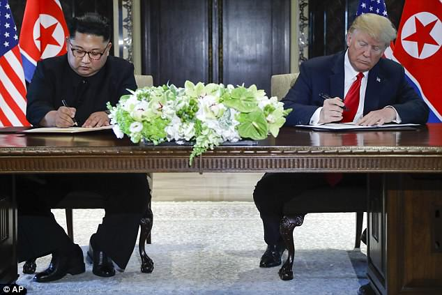Kim Jong-un and Donald Trump sign the statement after their meeting in Singapore