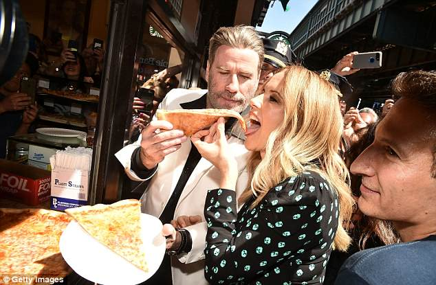 Travolta was joined by his wife Kelly Preston, who looked delighted to be biting down on the iconic pizza