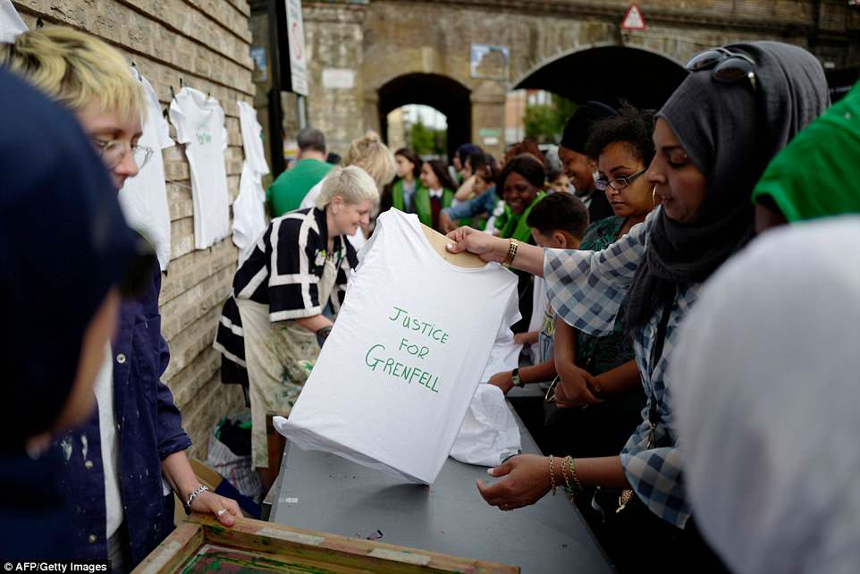 "People queue to get a screen-printed t-shirt, reading ""Justice 4 Grenfell"", near the Grenfell Tower"
