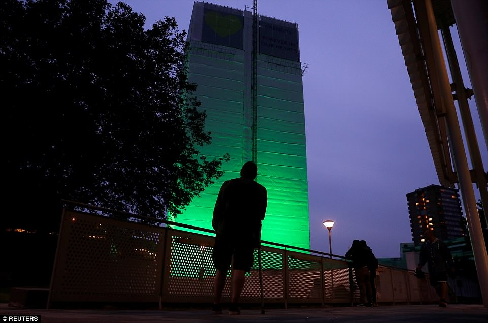 A man looks on at Grenfell Tower, which has now been covered and illuminated in green light as a tribute to the 72 residents who lost their lives a year ago tonight