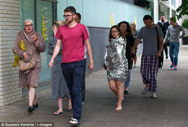 Residents are pictured returning to their homes following the blaze in South East London