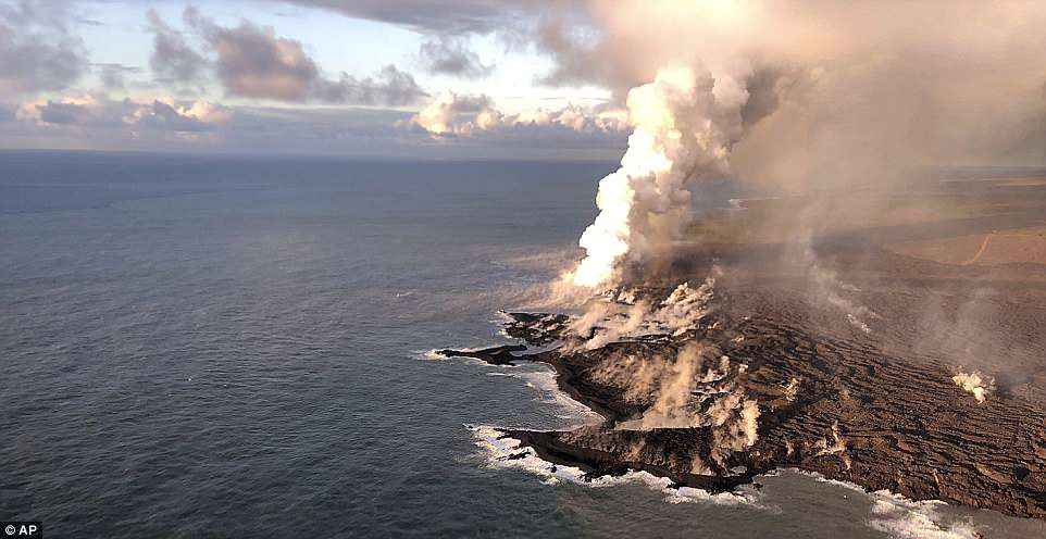 This photo provided by the U.S. Geological Survey shows where lava from Kilauea Volcano is entering the ocean and the resulting laze plume where lava is entering the sea at Kapoho on the island of Hawaii at dawn Wednesday, June 13