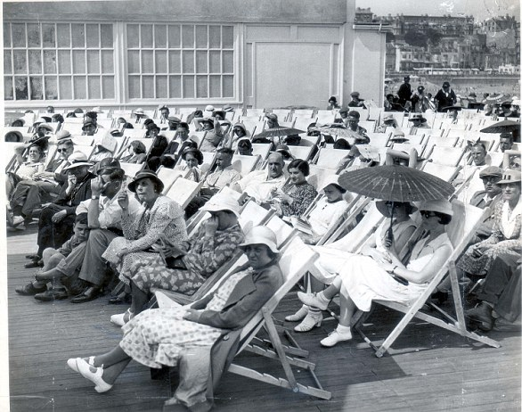 From the outset it was a popular tourist attraction, with visitors travelling from miles around (undated photo of tourists lounging on deck chairs at Hastings pier)