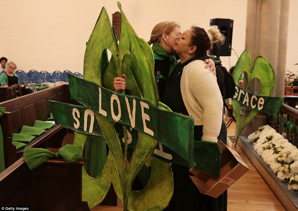 Two women clutching Grenfell symbols bearing the words love and justice embrace ahead of a moving service