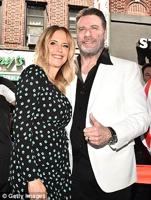 Thumb's up:The Saturday Night Fever actor wore a white blazer over a black shirt as she coordinated in a black dress
