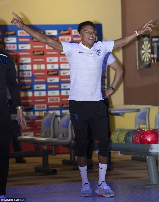 Jesse Lingard celebrates as some of the England players bowled at the media centre