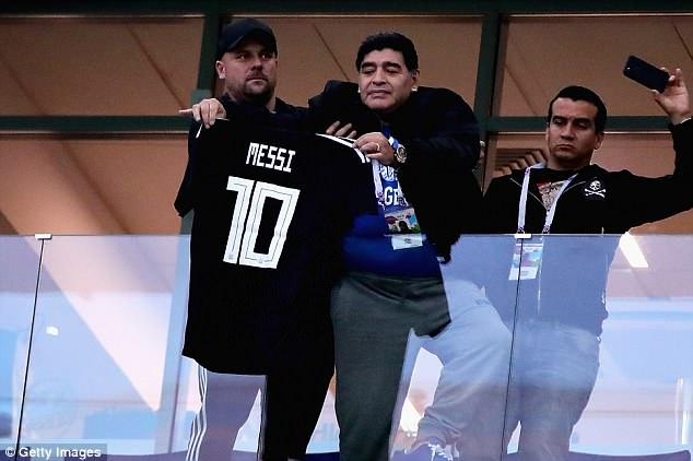 Maradona holds up his very own 'Messi No 10' shirt as he waits for the game to kick off