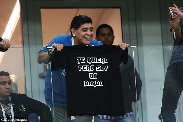 Diego Maradona holds up a shirt with lyrics from the song 'Te Quiero Pero Soy Un Bardo' (I love you but I'm a bard)